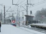 Ein 'Сапсан' (Sapsan) Velaro EWS1 fährt durch den verschneiten Bahnhof von Kolpino in Richtung Sankt Petersburg, 18.2.18