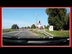 Annäherung per Strasse an den geschlossenen Bahnübergang in Borckenfriede. Nun beginnt das vermeintlich lange Warten darauf, daß der Bahnübergang wieder freigegeben wird. Zusehen ist der RE 3 von Stralsund kommend, der den Bahn&#2 ...